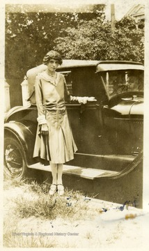 African-American student, Anna Frazier, poses next to an early automobile.