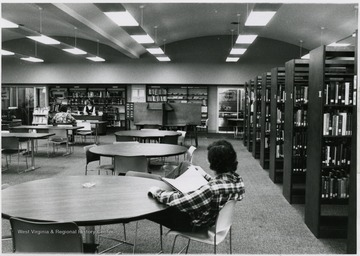 'Library on ground floor, moved downstairs to the bookstore ca. 1979. Mrs. Frank at the circulation desk.'