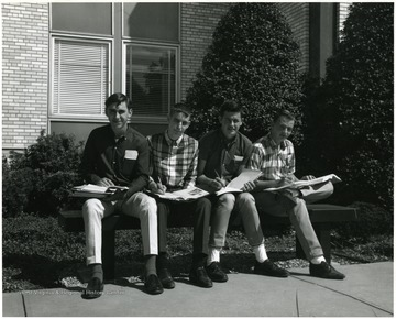 Four young men sitting outside on a bench studying in front of the Agriculture Building.
