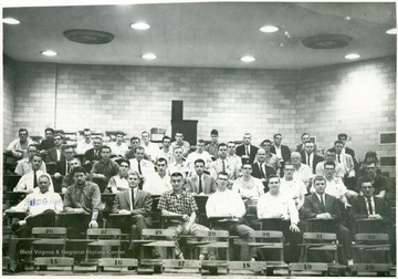 A Group portrait of graduates and faculty of the physics department at West Virginia University taken at what appeared to be one of University classroom; Danny McDonald, Nick Nicholson, Bill Coleman, Paul Errington, Aubry Hudgins, Frank Hoge, Bill, Roger Mersing Boelschevy, Yu Hak Hann, Gerry Huffman, Phil Pennington, Wade Temple Gefferson Marsh, Danny Sullivan, Dr. Charles Thomas, Pro. Douglas Williamson, Pro. Rexroad, Dr. Rex Ford.  (Not all the individuals in the photo are named, nor it is clear that which individual in the photo is named).