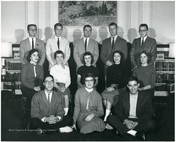 A group of students gathered in front of a fire place in Elizabeth Moore Hall.  Some students are named: Top Row from left to right 1) Unknown 2) Unknown 3) Unknown 4) 'Mike' Oliver 5) Unknown; Middle Row 1) Unknown 2) Barbara Sayre 3) Ruth Ann Walker 4) Carolyn Miller 5) 'Vickie' Vickers; Bottom Row --all unknown.