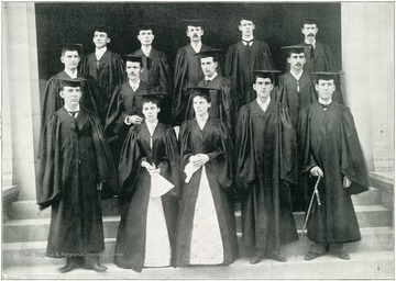 Group of students from the graduating class of 1895 pose in cap and gown. In the forefront of the photo are twins Anna and Stella White of Morgantown, W. Va., who were the first women to receive Bachelors of Science degrees at West Virginia University.The other graduates of the class are: W. B. Cutright (Morgantown, W. Va.); C. E. Carrigan (Wheeling, W. Va.); T. L. Davies (Gleville, W. Va.); M. E. Gorman (Rivesville, W. Va.); W. J. Holden (Glenville, W. Va.); S. S. Jacob, Jr. (West Liberty, W. Va.); G. H. A. Kunst (Weston, W. Va.); U. S. G. Kendall (Fairmont, W. Va.); T. M. Lavell (Pencoyd, Pa.); Russell Morris (Morgantown, W. Va.); P. B. Martin (Kingwood, W. Va.); J. B. Protzman (Morgantown, W. Va.); C. N. Ridgway (Hospital, Illinois); Silas Stathers (Wheeling, W. Va.); and J. F. Strader (Morgantown, W. Va.).