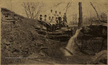 Group of students in a medical class pose by a small water fall near Falling Run, some are wearing long aprons; on the site now stand Business and Economic and Life Science Buildings. An inscription of 'Dr. J.F. Trippett died August 20, 1912' with a signature of Clyde Trippett, M.D. on the back.