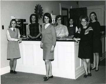 Members of Activities Board of Associated Women Students gather around a reception desk near the entrance of Elizabeth Moore Hall; 2nd from left Sudie Horman, 3rd from left Judy Skunda, 4th from left Becky Clise and 5th from left Carolyn Peluso.