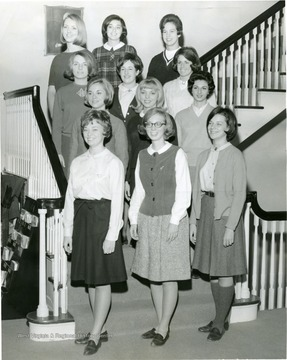 Members of Associated Women Students Activities Council pose on a staircase in Elizabeth Moore Hall.