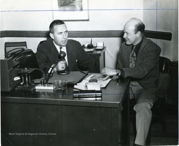 Two WVU faculty members sit at a desk while one on the left Joseph Gluck holds a microphone.