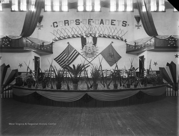 WVU Commencement Hall decorated with potted flowers and plants, garlands of lights, swags of fabrics and bows; on the backdrop the U.S. Flag and unidentified flag spread.  The Banner over the flags and a centerpiece of lights reads CORPS OF CADETS.