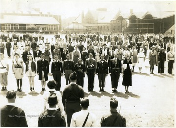 An assembly of R.O.T.C. cadets on a plaza (now Mountainlair Parking Area).  A row of cadets with different uniforms and sponsors are appeared to be receiving words.  In the background, Stewart Hall, Clark Hall and roofed stadium seats in where Mountainlair is located now are seen.