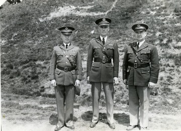 Three officers stand side by side by an embankment of Drill Field.