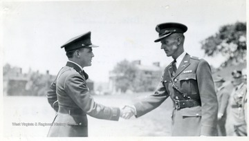 A cadet escorted with a sponsor receives a trophy and a congratulatory handshake from an Officer.