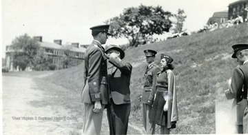 A cadet receives a badge from a civilian male.
