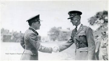 A cadet shakes hands with an officer.