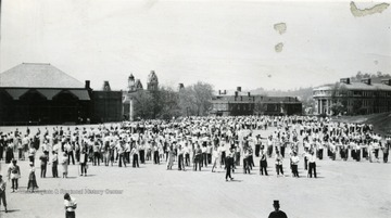 Some cadets are dressed in costume others dressed casual.  Oglebay Hall, Chitwood Hall and the towers of Woodburn and Martin Hall are seen in distance.