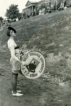A band member dressed in a female attire strikes a drum for audience.