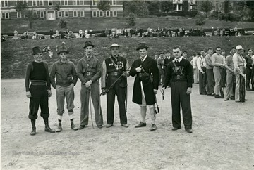 Group of cadets pose for a camera on Old Clothes Day, while onlookers watch them.