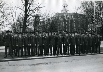 Members of Scabbard and Blade stand in a median across from Stewart Hall.
