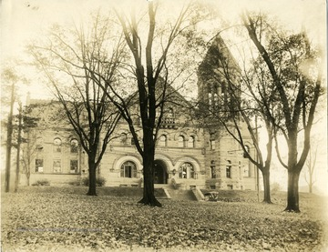 A view of Stewart Hall when it was used as library.  Over the central archway 'LIBRARY' is engraved.  A hooded car is parked in front of the building on University Avenue.  The photo is taken across from the street on a fall day.