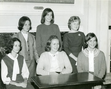 YWCA Officers pose in front of a fire place in Elizabeth Moore Hall; Left rear,  Royce Harworth (Heiskell); center Jennifer Brand.