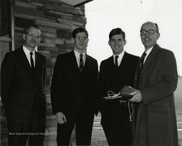 'Scene from the Mar. 23-27, 1967 international meeting of the Association of Women Students held here during the 100th Anniversary observance shows, from left to right: David Hess, director of student educational services and assistant provost of WVU; Jim Mullendore, president of the WVU student body; David C. Hardesty, former president of the WVU student body; and Edward Eddy, president of Chatham College in Pittsburgh.'