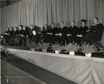 View of the platform at the Field House during the ceremonies. Left to Right: A.C. Spurr, Senator Chapman Revercomb, Wm. G. Thompson, Rev. C.W. Snyder, President James B. Conant of Harvard, President Stewart, President Vannevar Bush of the Carnegie Institution, Raymond E. Salvati, C.T. Neff, Jr., K. Douglas Bowers, Mrs. George D. Hill and Dr. Thomas L. Harris.