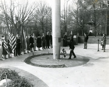 A wreath is placed by the mast of the U.S.S. West Virginia in Memorial Plaza. Martin hall is pictured in the background on the right. Elizabeth Moore Hall can be seen in the background on the left.