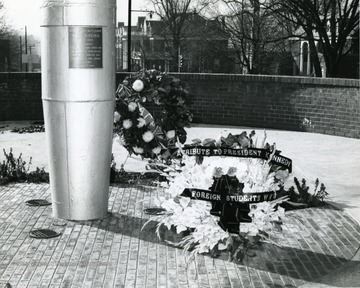 Shown here are two wreaths placed at the bottom of Mast in Memorial Plaza.  One wreath has 'A Tribute to President Kennedy from Foreign Students WVU'.