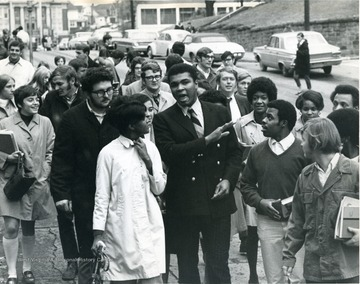 Boxing champion Mohammed Ali walks down University Avenue with students.