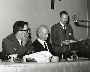 'Two time winner of the Nobel Peace Prize, Linus Pauling (center), is introduced by moderator Vincent Traynelis, chairman of the WVU Dept. of Chemistry (right), as symposium committee chairman Guy Stewart, WVU prof. of Journalism (left), watches at the Science-Writing symposium Oct. 6, 1967.