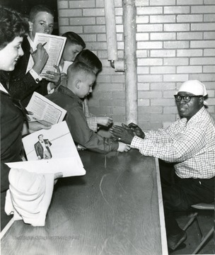 Armstrong, Louis, legendary jazz musician signs autographs for eager fans.