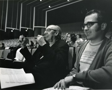 Aaron Copland sits next to a student in concert hall at Creative Arts Center.