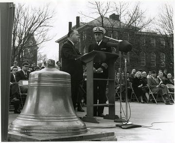 West Virginia University President James G. Harlow (left) and Naval Reserve Captain Marlyn E. Lugar are shown at dedication ceremonies for the bell from the armored cruiser and battleship U.S.S. West Virginia. In the background is Woodburn Hall and Chitwood Hall.