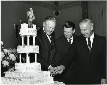 '100th Anniversary Birthday Dinner on Feb. 13, 1967.  The banquet was delayed six days due to an unexpectedly heavy snow storm.  Cutting the birthday cake are, left to right: Governor Hulett Smith, acting WVU President Harry B. Heflin, and Congressman Arch A. Moore.'