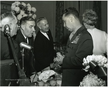 'Feb. 13, 1967 WVU Birthday Dinner, from left to right: Ray Wilkins; Joe Gluck, WVU Director of Student Affairs; Congressman Arch Moore; Marine Corps Brig. Gen. and WVU alumnus General Earl E. Anderson.  Woman with back turned is unidentified.'