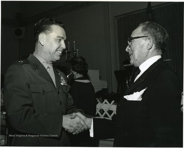 'WVU graduate and Marine Corps Brig. Gen. Earl E. Anderson shakes hands with Harry Goldsmith at WVU Birthday Dinner on Feb. 13, 1967.'