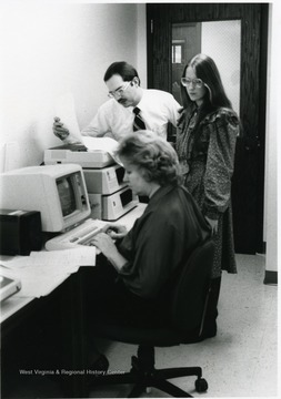 Jeannie Grimm at the computer and Susan Beates Hansen standing.