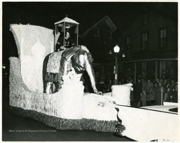 A Football player rides on a float with a golden elephant.