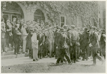 Students protest the WVU administration's decision not to cancel the spring semester final exams as many other colleges had decided to do after the United States officially entered World War I on April 6th. Most male students would either enlist or be drafted as soon as possible forcing them to leave school before the end of the semester.