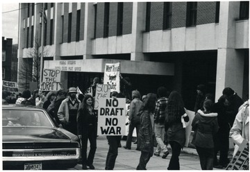 Female with 'Stop the Draft' sign is Alice Bell.