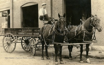 Man on horse drawn wagon outside of the Old Buick Garage on Water Street in Clarksburg, West Virginia.