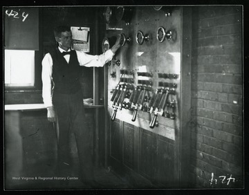 "An unidentified man demonstrates a ""switch board"" at Martin Hall."