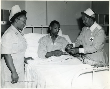 'Chief Nurse 1st Lt. Elizabeth T. Dozier, Rt. #1, Box 79, Eastover, South Carolina, looks on while Pfc. Calvin Williams, 1836 'E' Street, Fresno Calif., pleasantly passes away hours with handcraft in Lockbourne Army Base Station Hospital, Columbus, Ohio, with the aid of Franklin County Red Cross Chapter Gray Lady, Mrs. Lillie B. Williamson, 170 North Champion Avenue, Columbus, Ohio.'