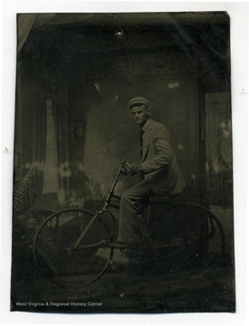 A portrait of student, Dille, Thomas R. riding a bicycle appears to be taken at studio.