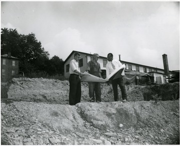 Two men and President Richard McKinney (right) look at blue prints for a student construction project.
