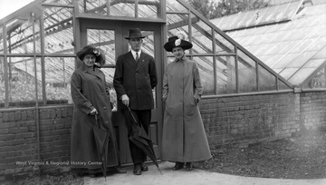 A. J. Dadisman in the middle with Nail and Allender in front of green houses.