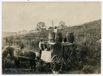 Farm workers in a field with a horse drawn cart with barrels.