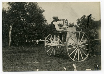 A man rides on a spray cart at Guseman's orchard.