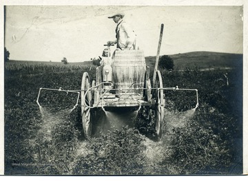 A man and a little girl on spraying cart.