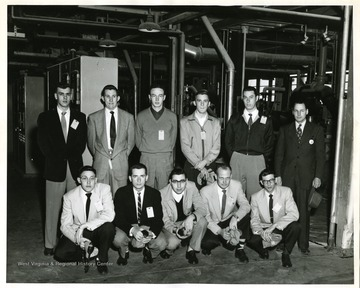 Group portrait of West Virginia University College of Pharmacy students visiting  Calco Chemical Plant in Willow Island, W. Va. See A&M 977 for correspondence regarding this trip. Kneeling:  Robert Lewis, Donald Douglas, Samuel Argentine, Benton Smith, William Hammett; Standing: William Shumate, Rudy Harman, Robert Robinson, Jack Riggs, Herbert Rothlisberger, Calco Rep.