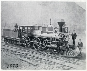 'Westward Ho - Delivered to Va. Central July 1857.  Picture taken at Winifred Junction 1870.  Andy F. Southworth, engineer, 'Barney' Hagen, fireman, standing on left side of pilot with tallow pot in his hand.'