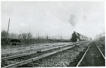 'Storms out of Alderson, towards Hinton on a winter day in 1909, pulled by an Atlantic (4-4-2) Locomotive, as a freight recedes into the background.